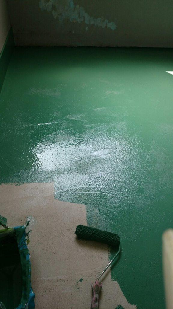 床に緑色の塗料を塗る写真